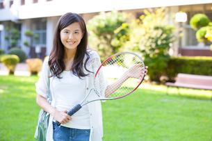 テニスラケットを持って微笑む女子大学生の写真素材 [FYI02002474]