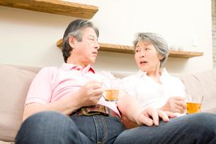 ソファでお茶を飲むシニアカップルの写真素材 [FYI02002564]