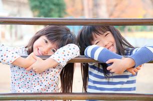 遊具につかまって微笑む女の子2人の写真素材 [FYI02002574]