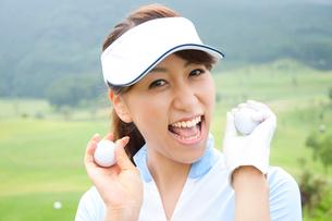 ゴルフボールを持って微笑む女性の写真素材 [FYI02002575]