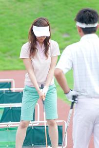 ゴルフ練習場でレッスンを受ける女性の写真素材 [FYI02002629]