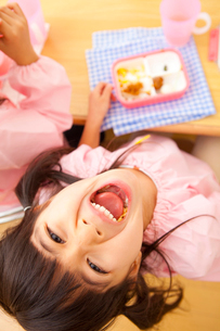お弁当を食べながらおどける幼稚園女児の写真素材 [FYI02002643]