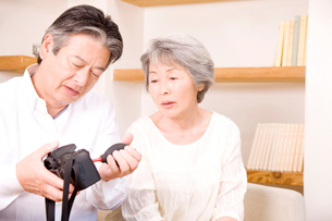 シニア女性と会話をしながらカメラの掃除をするシニア男性の写真素材 [FYI02002702]