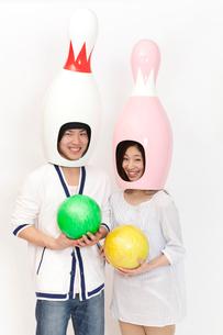 ボウリングのピンの被り物をかぶって微笑むカップルの写真素材 [FYI02002706]