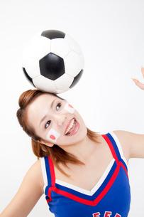 サッカーボールを頭に乗せるチアガールの写真素材 [FYI02002725]