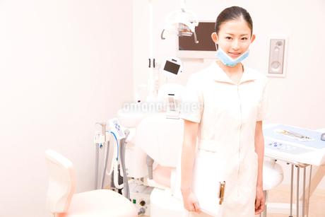 デンタルユニットの前に立ち微笑む歯科衛生士の写真素材 [FYI02002770]