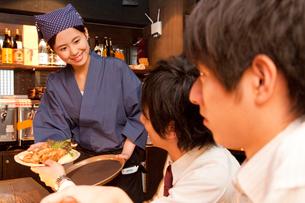 男性客に料理を渡す居酒屋店員の写真素材 [FYI02002822]