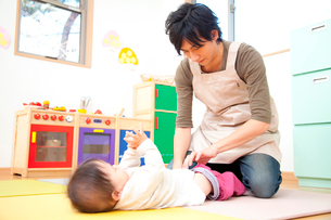 乳児のおむつ替えをする男性保育士の写真素材 [FYI02002995]