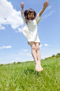 草原でジャンプする女の子の写真素材 [FYI02003105]