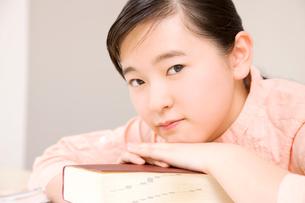 辞書に顔をのせる女子中学生の写真素材 [FYI02003424]