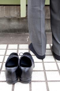 飛び降り自殺を図るビジネスマンの足元の写真素材 [FYI02003438]