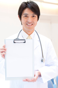 カルテのメッセージボードを持つ男性医師の写真素材 [FYI02003478]