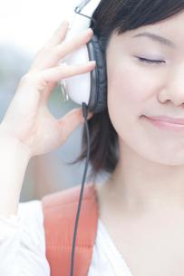 ヘッドフォンをして目を閉じる女子大生の写真素材 [FYI02003492]