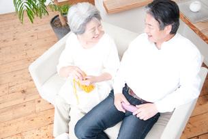 編み物をするシニア女性と笑顔のシニア男性の写真素材 [FYI02003520]