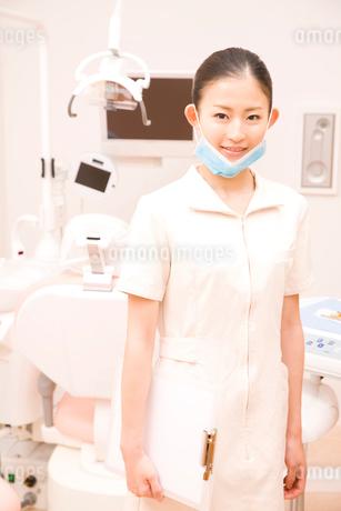 デンタルユニットの前に立ち微笑む歯科衛生士の写真素材 [FYI02003927]