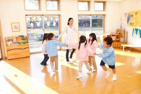 輪になって踊る幼稚園教諭と幼稚園児の写真素材 [FYI02003948]