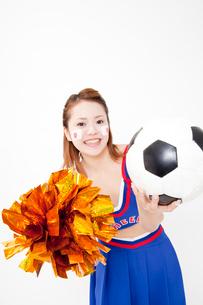 サッカーボールを持って微笑むチアガールの写真素材 [FYI02004056]