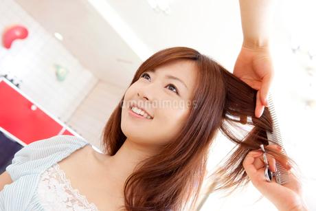 美容師に髪を梳かしてもらう女性の写真素材 [FYI02004073]