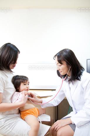 子供に聴診器を当てる小児科医の写真素材 [FYI02004085]