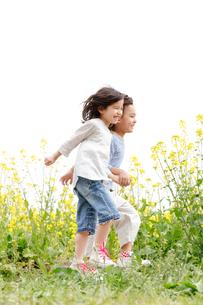 菜の花畑で手を繋ぎスキップする男の子と女の子の写真素材 [FYI02004210]