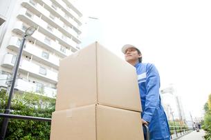 台車で荷物を運ぶ引越し業者の写真素材 [FYI02004295]