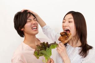 野菜を持った男性と骨付き肉を持った女性の写真素材 [FYI02004390]
