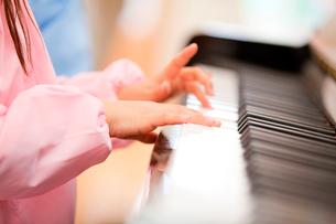 ピアノを弾く幼稚園女児の手元の写真素材 [FYI02004395]