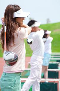 ゴルフ練習場でスイングする男女の写真素材 [FYI02004445]