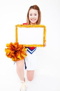 メッセージボードを持って微笑むチアガールの写真素材 [FYI02004574]