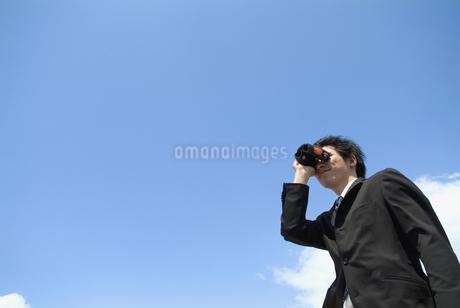 双眼鏡を覗くビジネスマンの写真素材 [FYI02004725]