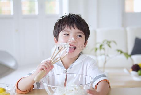 クリームを舐める男の子の写真素材 [FYI02005337]