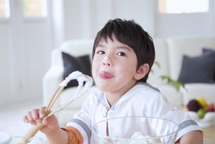クリームを舐める男の子の写真素材 [FYI02005366]