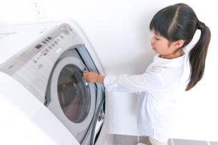洗濯機をあけようとする女の子の写真素材 [FYI02005618]