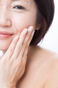 頬に手を当てるミドル女性の写真素材 [FYI02005619]
