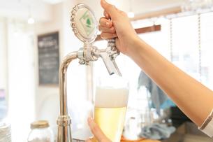 サーバーでビールを注ぐカフェ店員の写真素材 [FYI02005828]