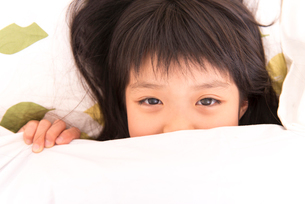 布団で顔を隠す女の子の写真素材 [FYI02005874]
