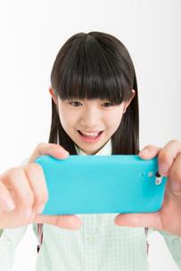 スマートフォンを操作する女の子の写真素材 [FYI02005984]