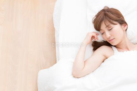 ベッドで眠る女性の写真素材 [FYI02006056]