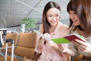 航空チケットを確認し合う女性達の写真素材 [FYI02006081]