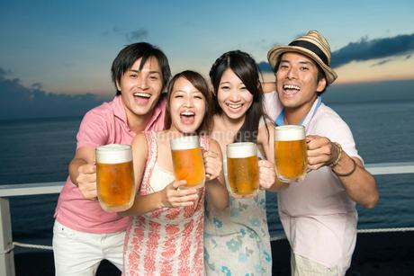 ビールで乾杯する男女4人の写真素材 [FYI02006186]