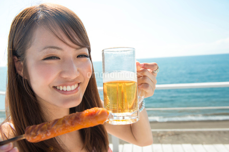 ビールを持ちながらフランクフルトを食べる女性の写真素材 [FYI02006202]