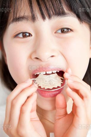 歯の矯正器具を入れる女の子の写真素材 [FYI02006216]