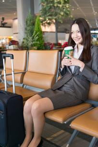 空港のラウンジでコーヒーを飲むOLの写真素材 [FYI02006341]