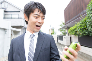 スマートフォンを触るビジネスマンの写真素材 [FYI02006460]
