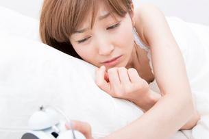 目覚まし時計を確認する女性の写真素材 [FYI02006486]