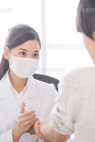 患者に注射を刺す女医の写真素材 [FYI02006500]