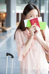パスポートとチケットを持って微笑む女性の写真素材 [FYI02006513]