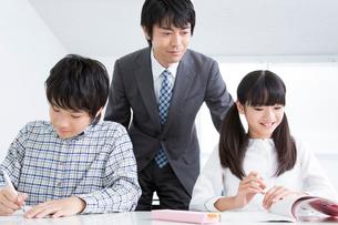 勉強する小学生と指導する教師の写真素材 [FYI02006592]