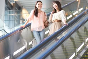空港のエスカレーターに乗る女性2人の写真素材 [FYI02006668]