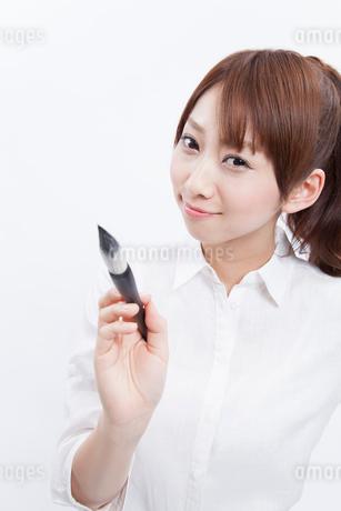 筆を持って微笑む女性の写真素材 [FYI02006796]